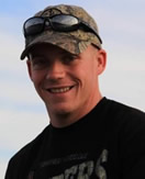 A young White man is wearing sunglasses and a camoflauge baseball hat is smiling into the camera.