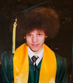Christopher Kalonji is pictured proudly sporting his high school graduation cap high on his afro.