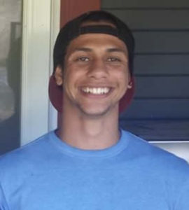 A happy young Black man wearing a baseball cap backwards is smiling into the camera