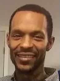 A Black man is facing the camera and smiling.